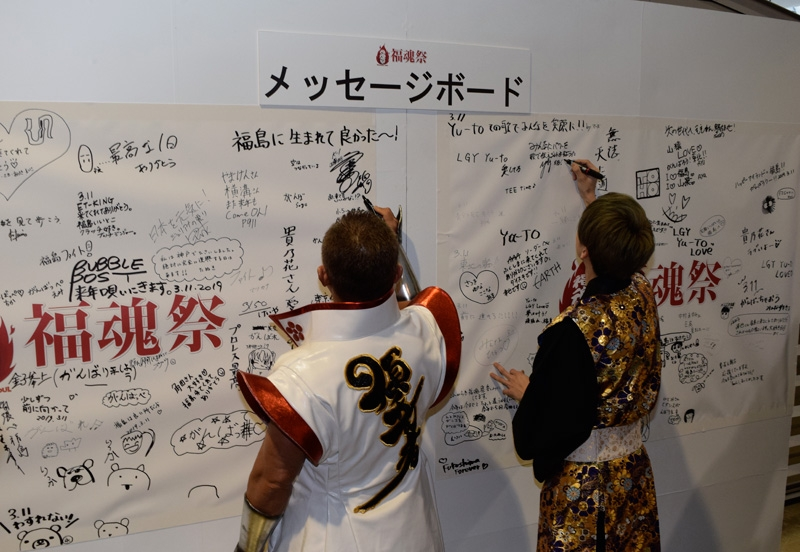会場内のメッセージボードに福島への想いをつづる角田さん、大西さん。