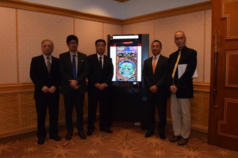 フィリピン進出を実現にこぎつけたアジア・アミューズメント開発の経営陣と、第1号店をオープンする松田氏(右から2番目)。中央はフィリピン仕様の遊技機『SONAR』。