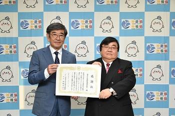 感謝状を受け取った伊坂重憲理事長(右)と、贈呈した神奈川県交通安全協会の石坂浩二会長(左)。
