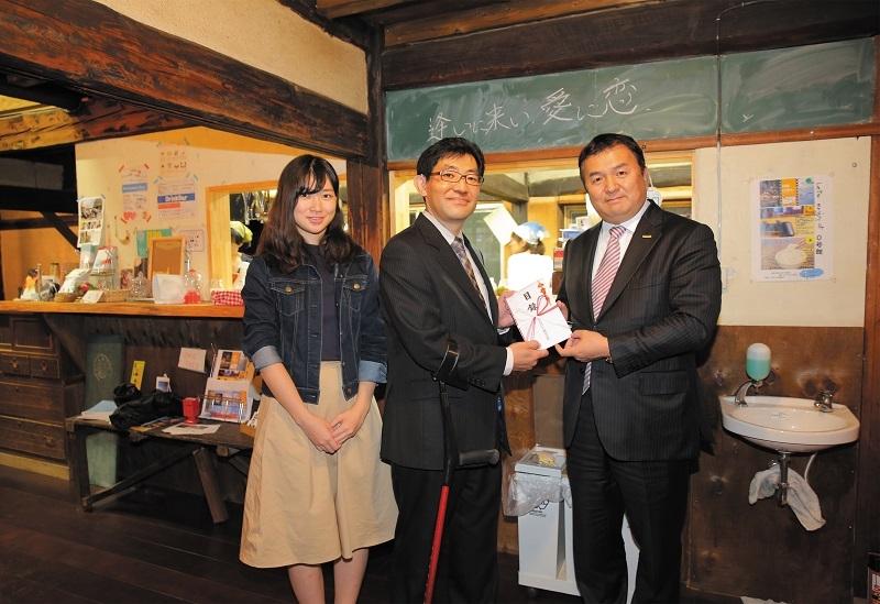 「高崎子ども食堂」の石北洋一代表(中央)へ、NEXUSの齊藤人志社長(右)から支援金目録が手渡された。