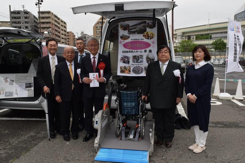 贈呈した福祉車両と福祉団体関係者と記念撮影に応じる伊坂会長。