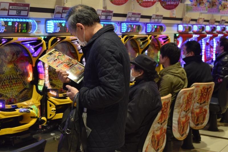遊技説明を手に究極アナログのゲームフローに見入る中高年ファン。