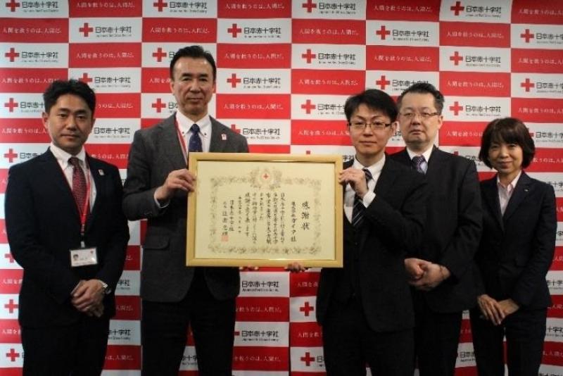 日本赤十字社から感謝状を受け取る小林課長代理(写真右)。