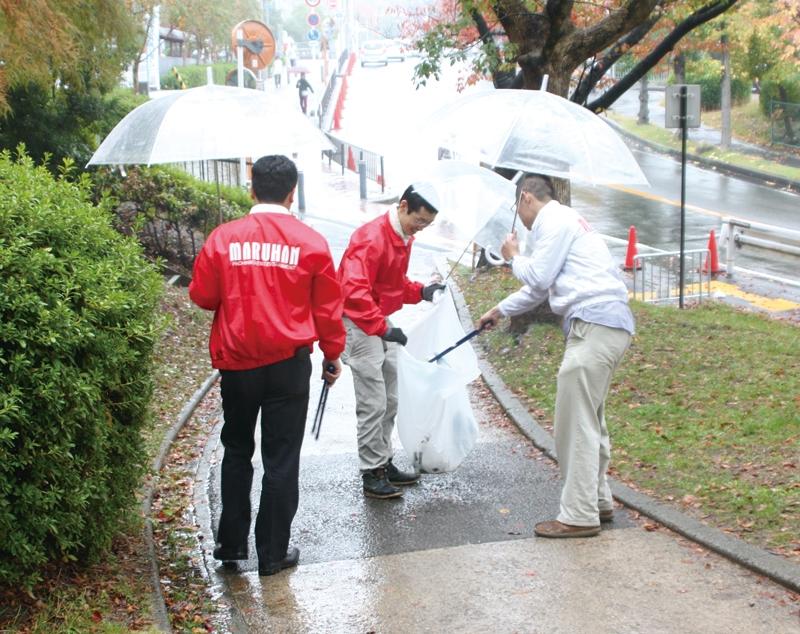 あいにくの雨の中、傘を片手に会場周辺の清掃活動を行った。