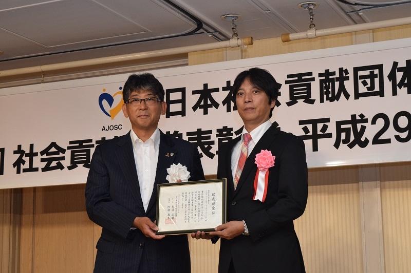 特命助成としてRSNの西村直之代表(右)に阿部恭久理事長(左)から助成認定証が贈られた。