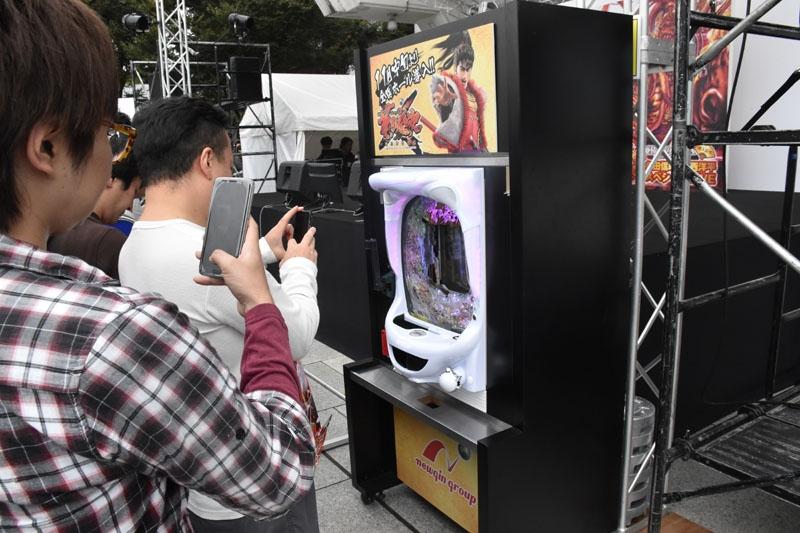 新機種の筐体を写真に収める参加者。