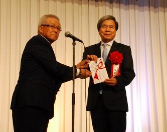 熊本県知事に寄付金を贈る岩下会長(写真左)