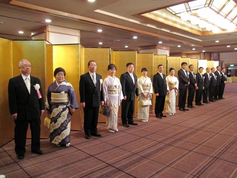出迎えに立つ同社幹部陣。創業者で現相談役の松波廣和氏(左)、古宮重雄会長、松波明宏社長、村上浩取締役は夫人を伴って並んだ。