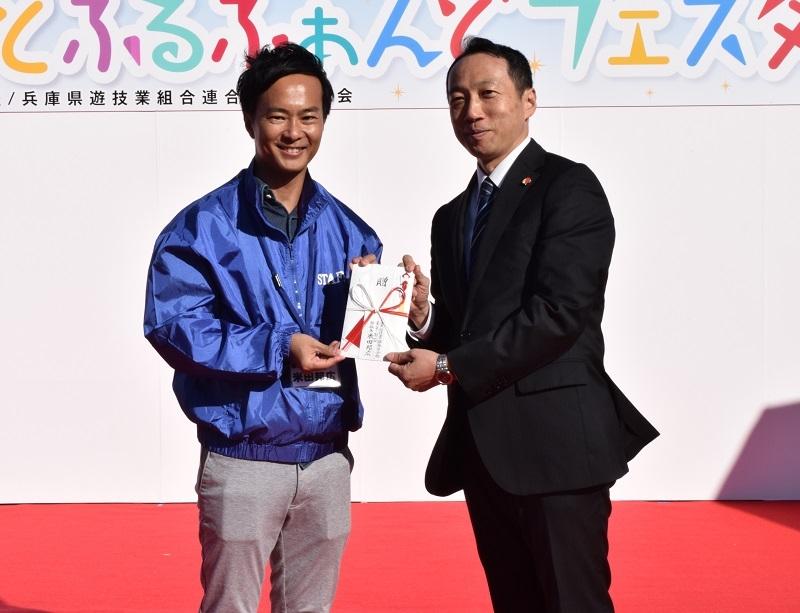 「こうべ障害者音楽フェア2017ジョイフルコンサート」に対して支援金をおくった。写真左が兵遊青の米田邦広部会長。