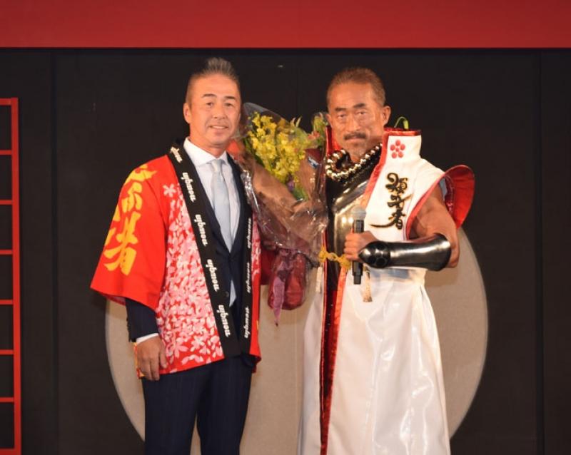 ボディビル大会の優勝をたたえ、角田さんに花束を贈るニューギン販売・笹本専務(左)。