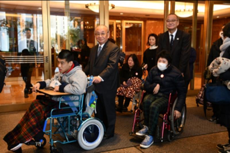 横浜市内で行われた「車いす空の旅・バスの旅事業」(1/26〜27)の出発式では、江川明裕副会長が見送る中、肢体不自由児10名とその家族、他ボランティアなど20名が千葉方面の旅に出発した。