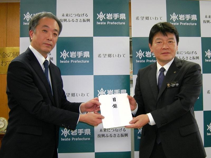 岩手県保健福祉部の八重樫幸治部長に目録を手渡した盛岡ゾーンマネジャーの富永浩之さん(左)。