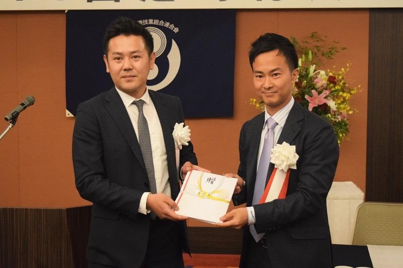 米田新部会長(写真右)から退任する北本部会長(写真左)に記念品が贈呈された。