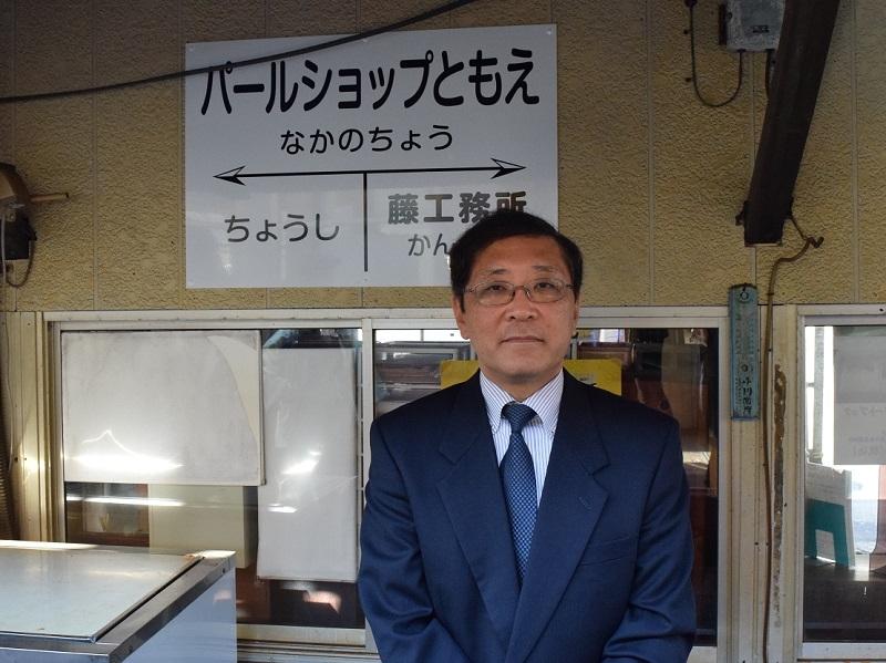 「パールショップともえ 仲ノ町駅」駅舎看板前で写真撮影に応じる銚子電鉄の竹本代表取締役。