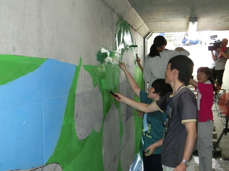 猛暑の中、山県市の魅力を描いた壁画の色塗りに汗を流した。